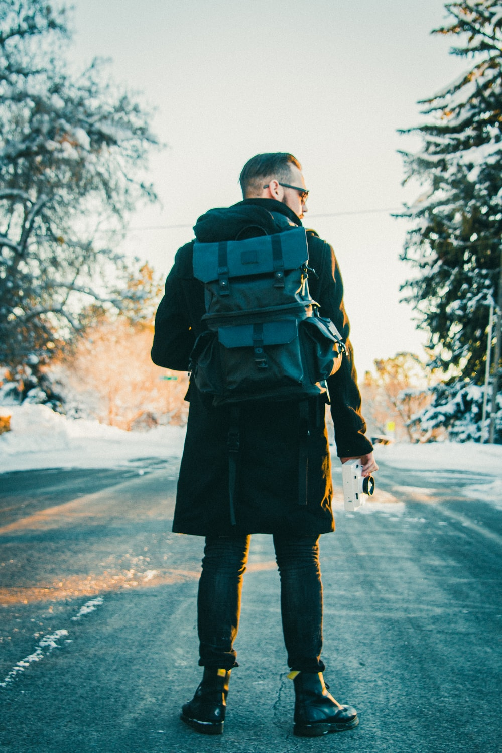 man wearing backpack in middle of the road