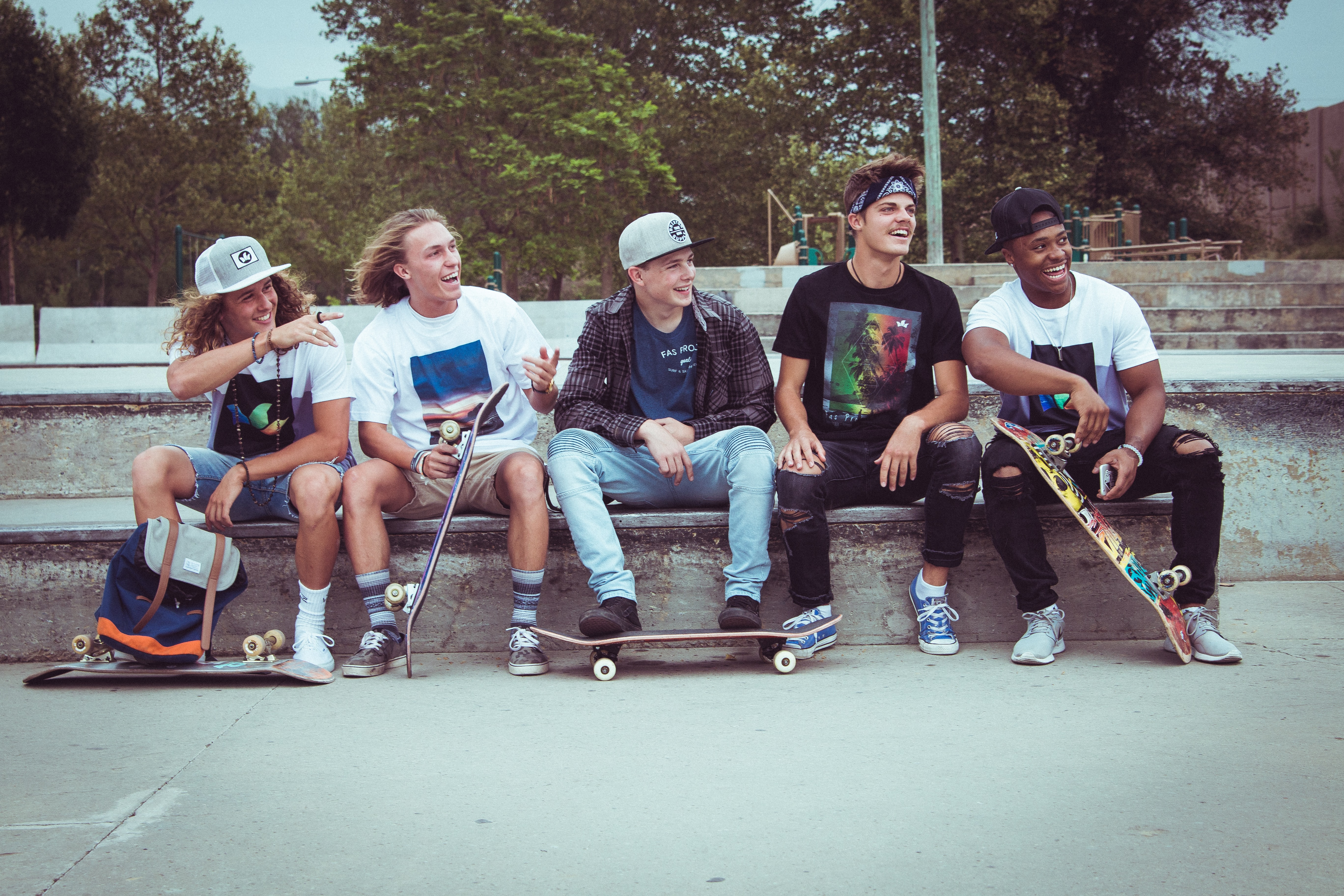 five group of men sitting together with their skateboards