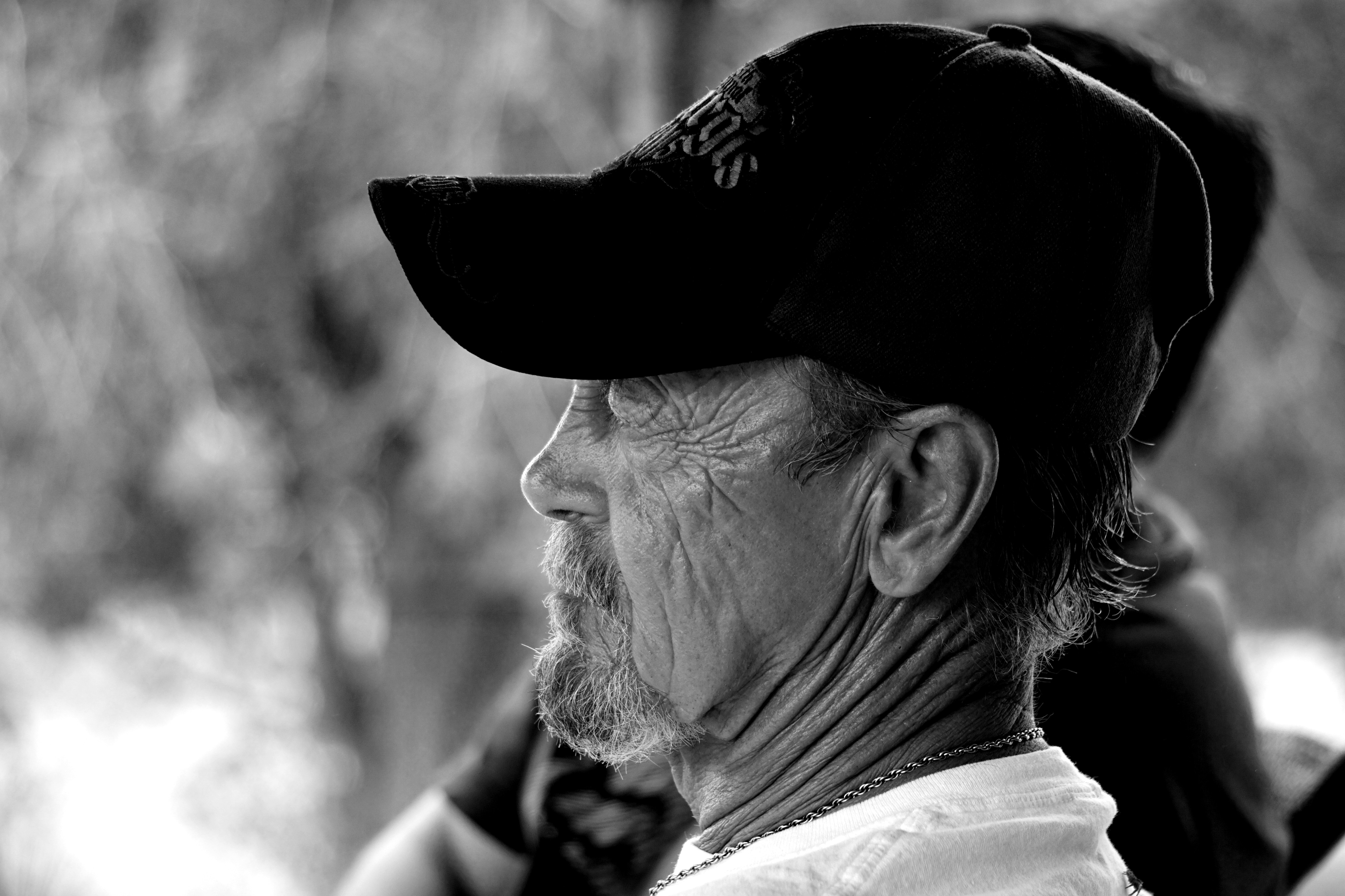grayscale photography of man wearing black cap