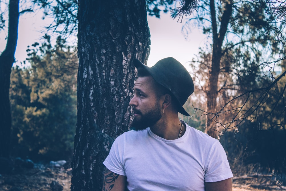 man leaning on brown tree wearing black fedora hat and white crew-neck shirt looking to side