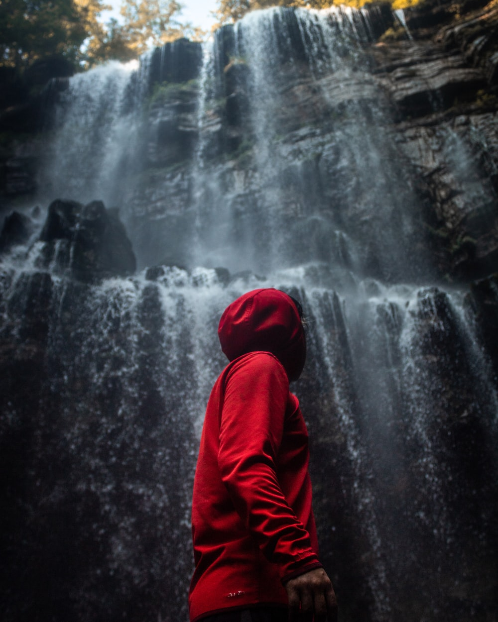 man in hooded jacket standing in front of waterfalls
