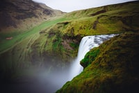 waterfall between green field during daytime