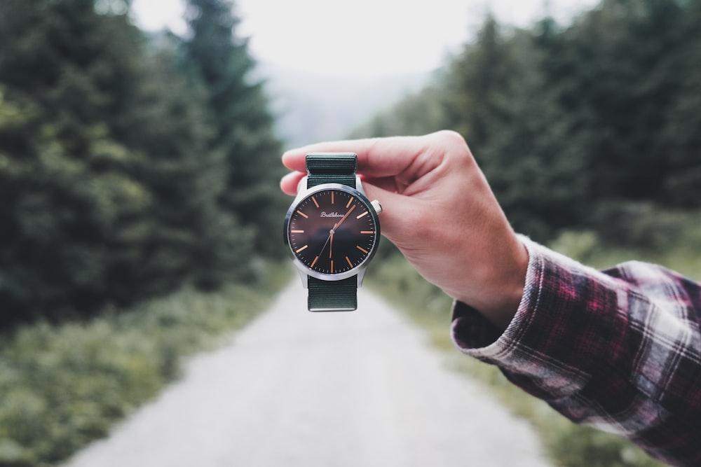 person holding round black analog watch