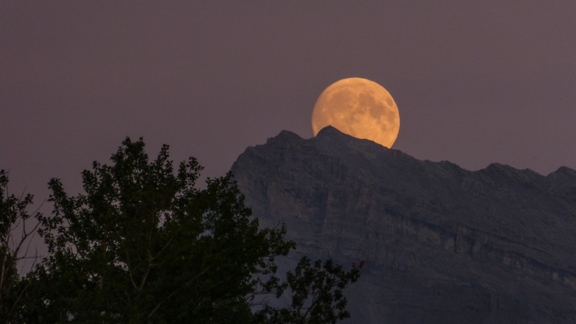 Image Credits: Unsplash /  Kym MacKinnon/vixenly | Ful moon behind mountain
