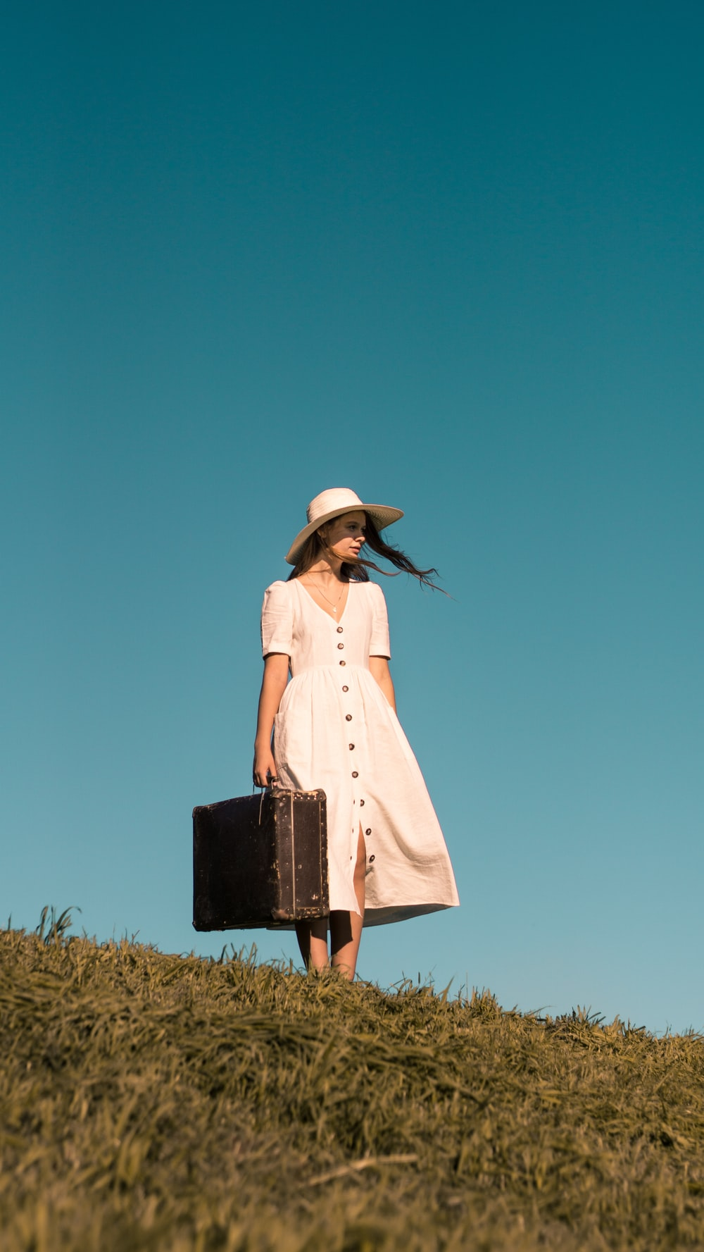 woman standing on green grass holding brown leather suitcase wearing white button-up dress