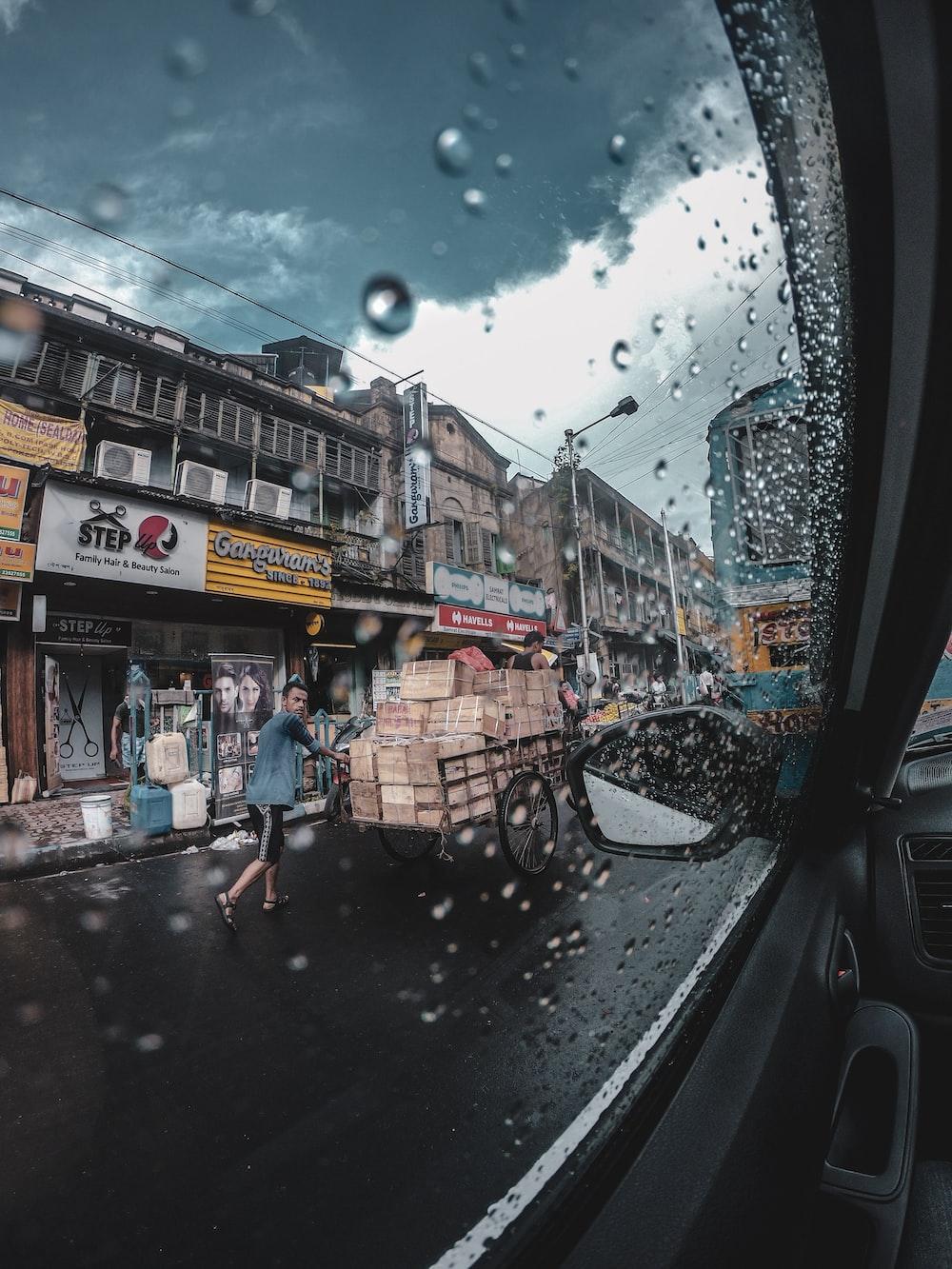 man pushing cart on road