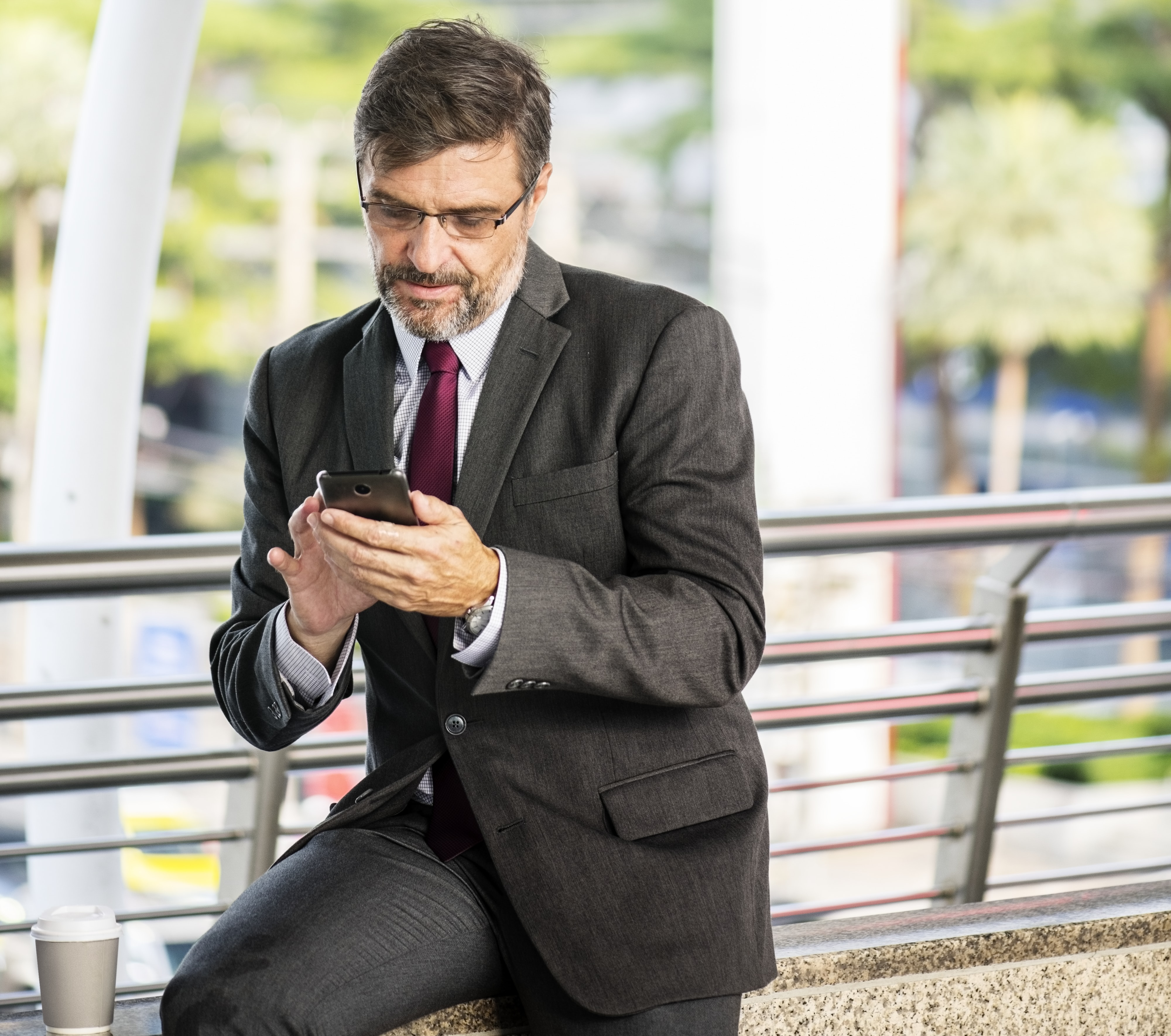 man in black formal suit holding black smartphone