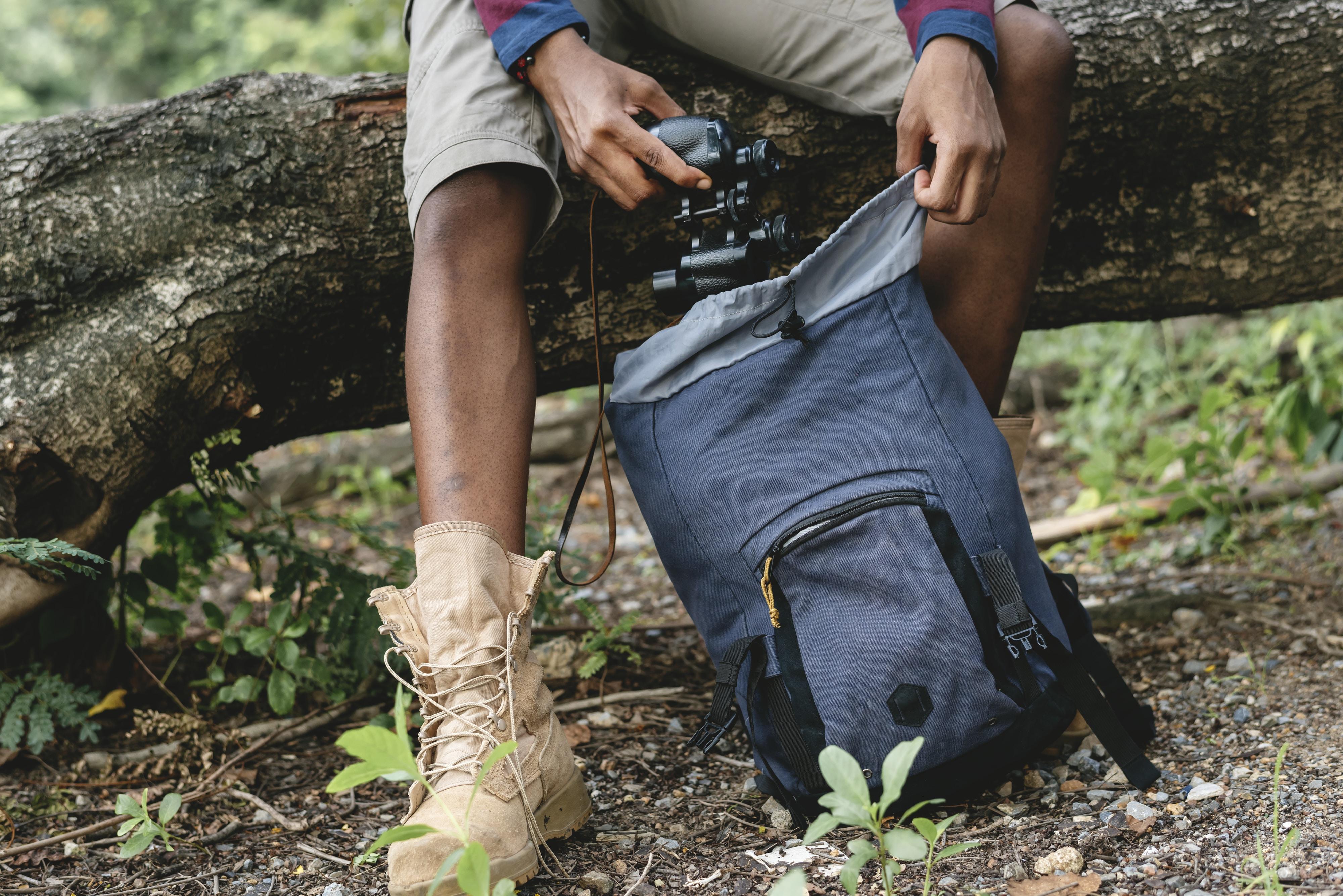 man holding black camera and gray camping backpack