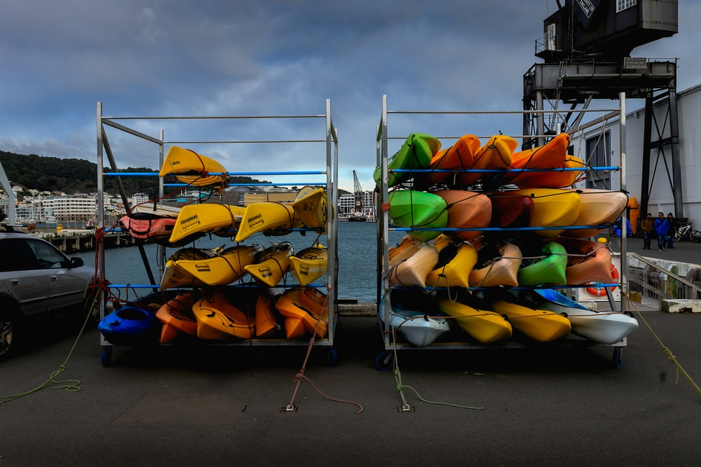 assorted-color kayak lot piled on racks