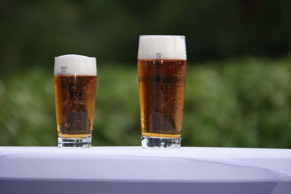 two conical clear pint glasses on white surface