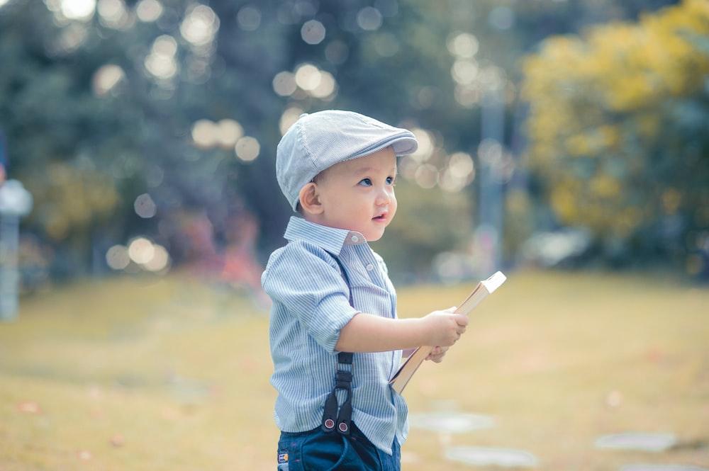 boy holding book during daytime
