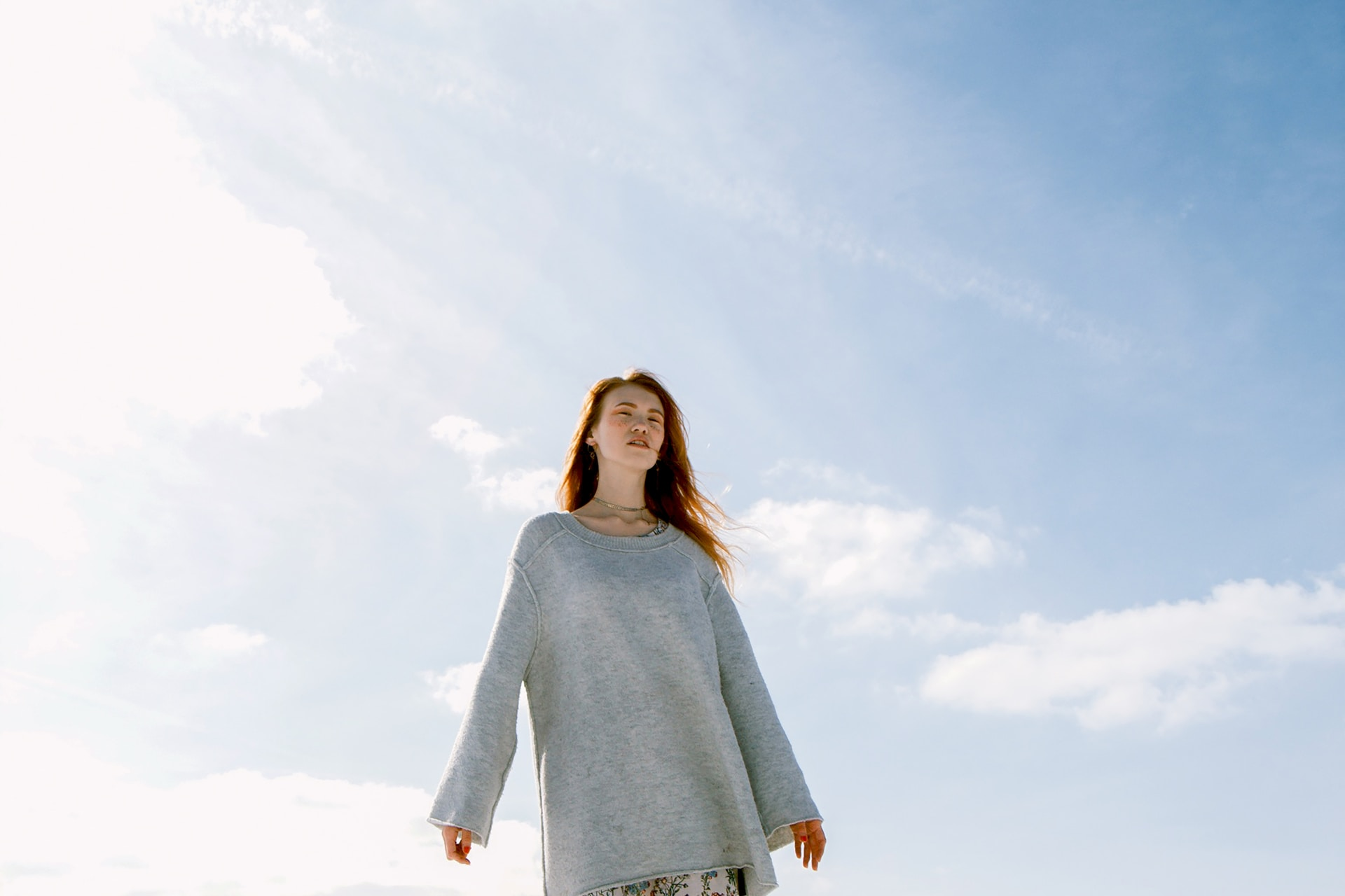 woman in gray crew-neck long-sleeved shirt standing on snowfield