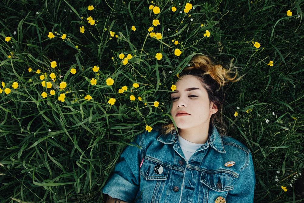 woman in blue chambray jacket lying on green grass