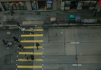 high angle photography of several people waking on concrete road