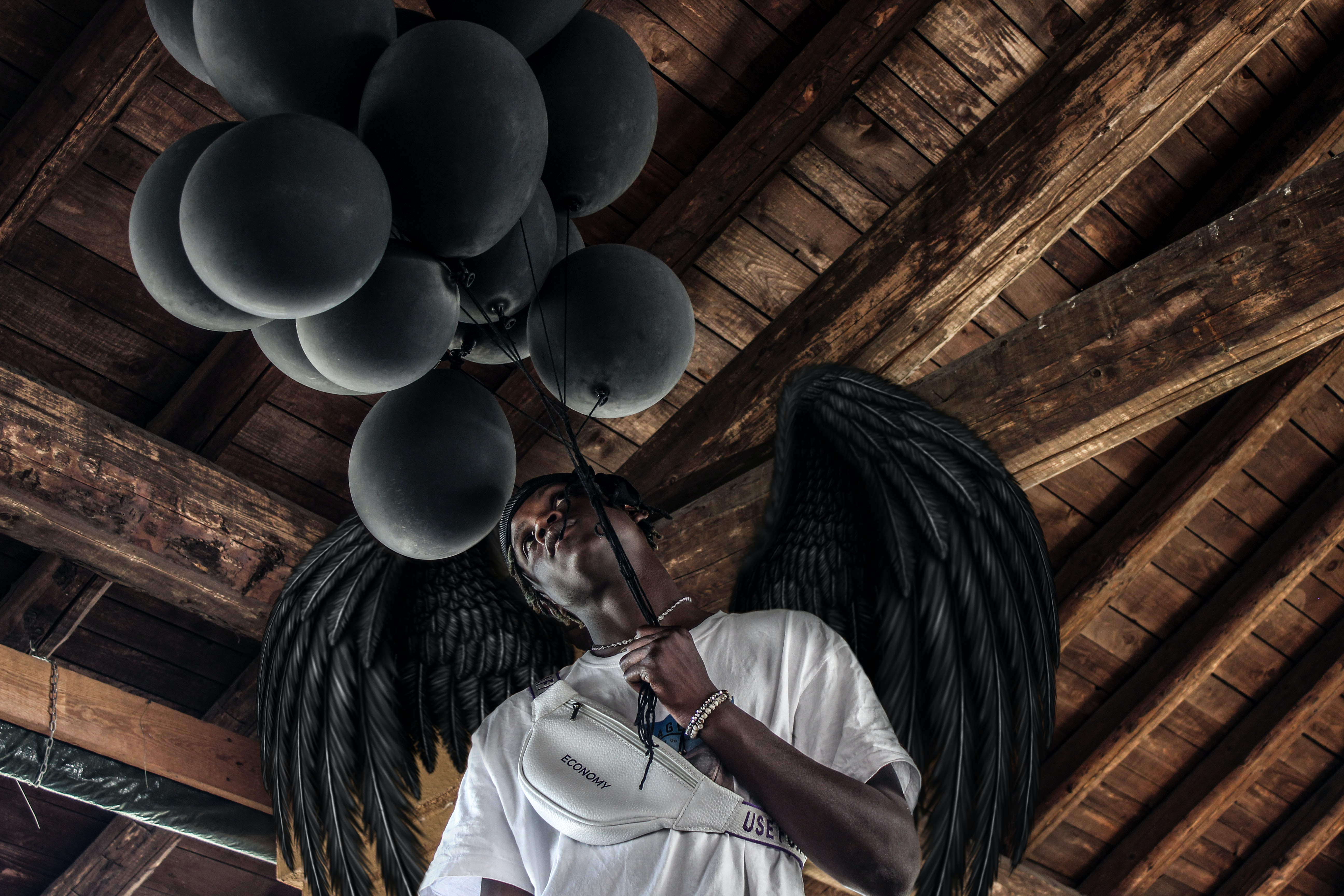 man wearing white shirt holding balloons with wings