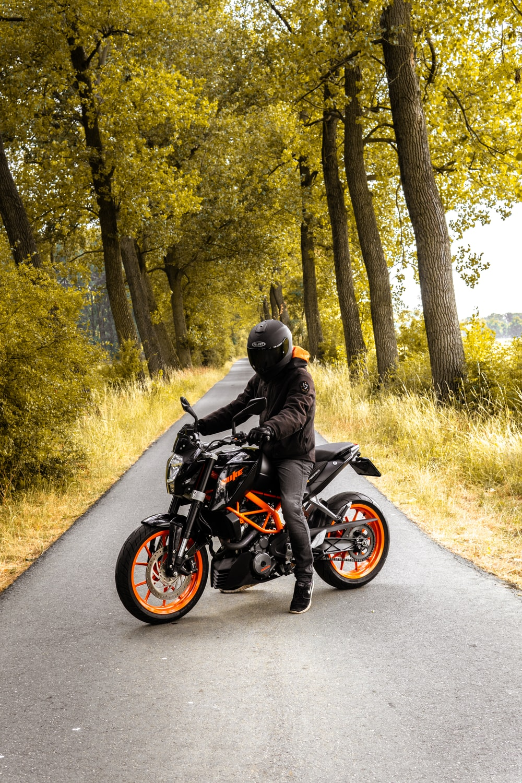 man riding black and orange motorcycle beside trees