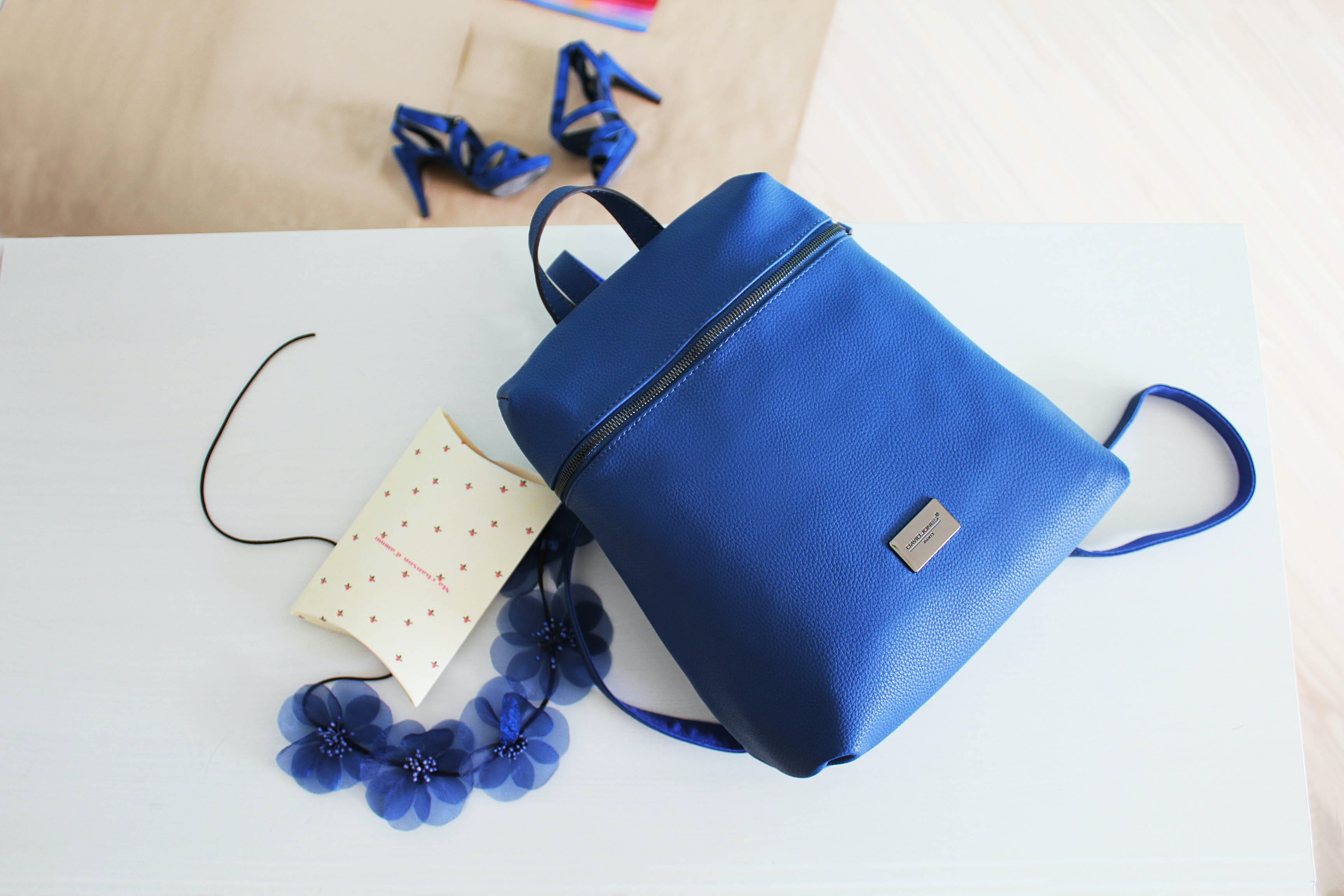 blue leather backpack placed on white wooden table