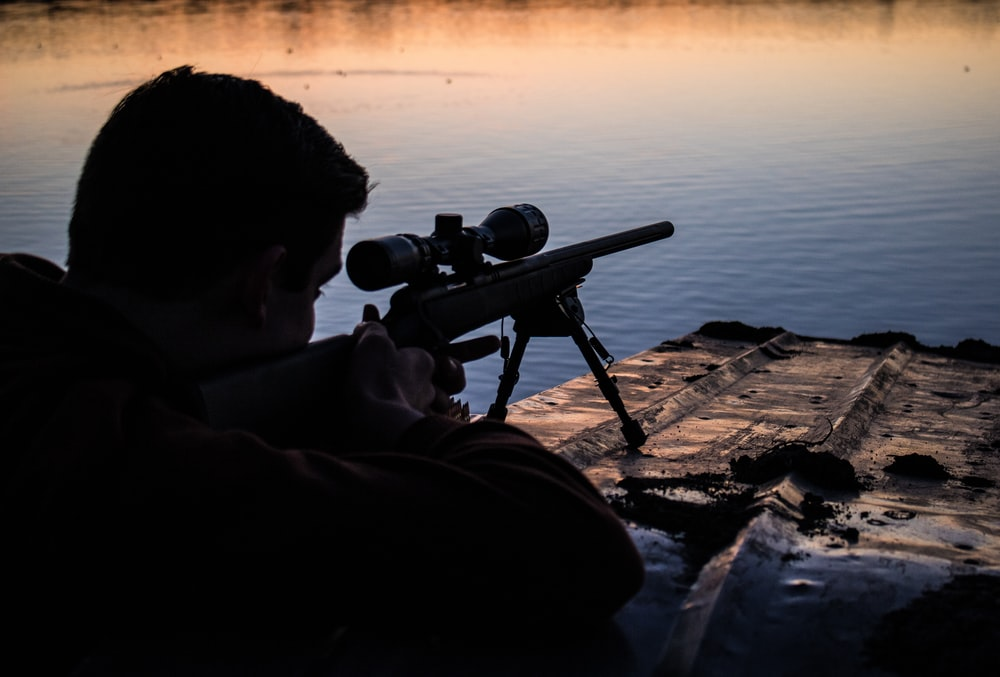 man aiming sniper rifle at target