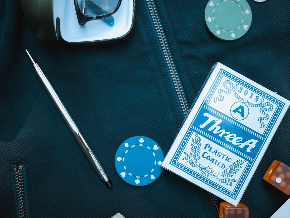 poker chip beside playing card box