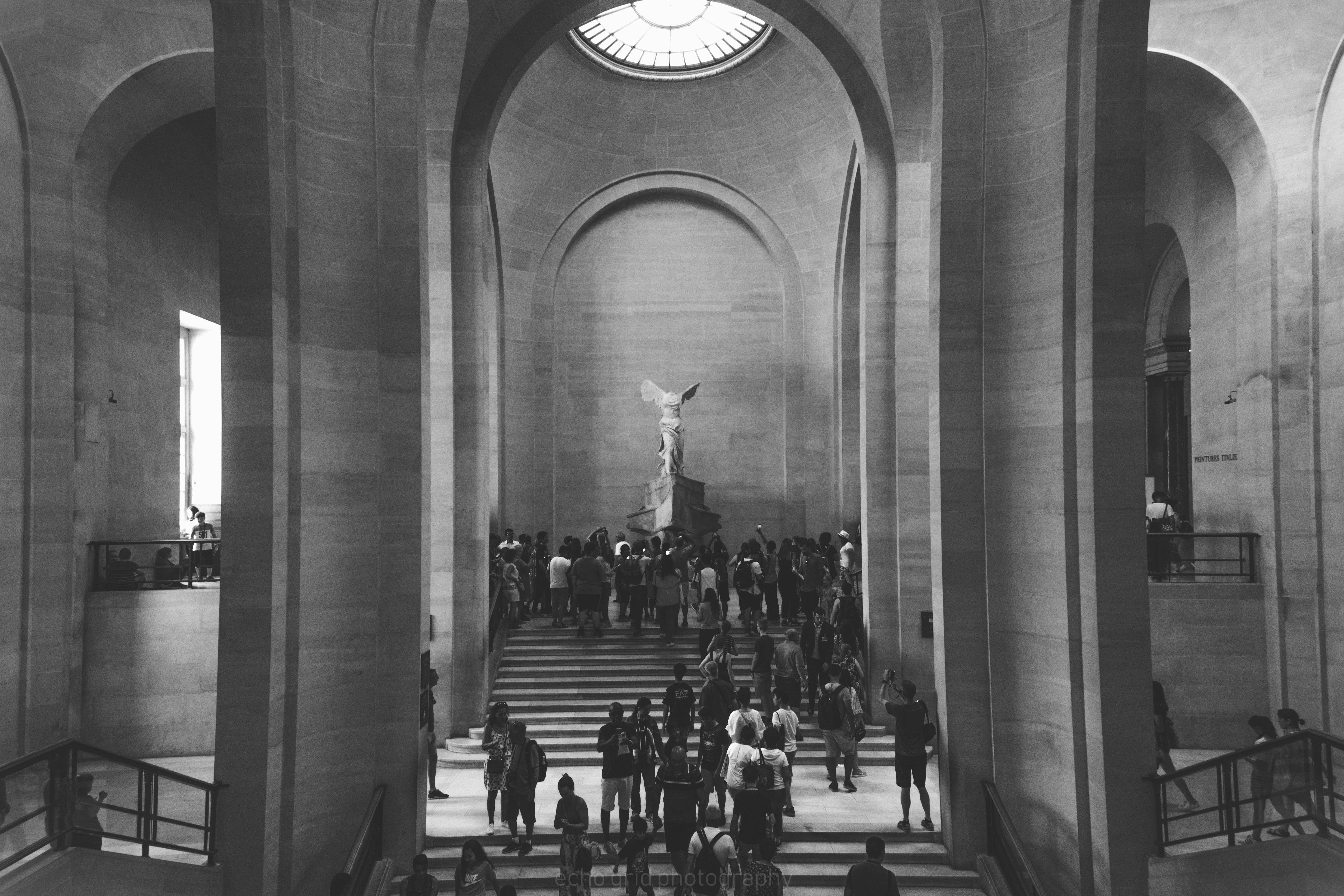 grayscale photo of people walking up the stairs inside building