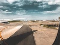 photo of white airplane on runway