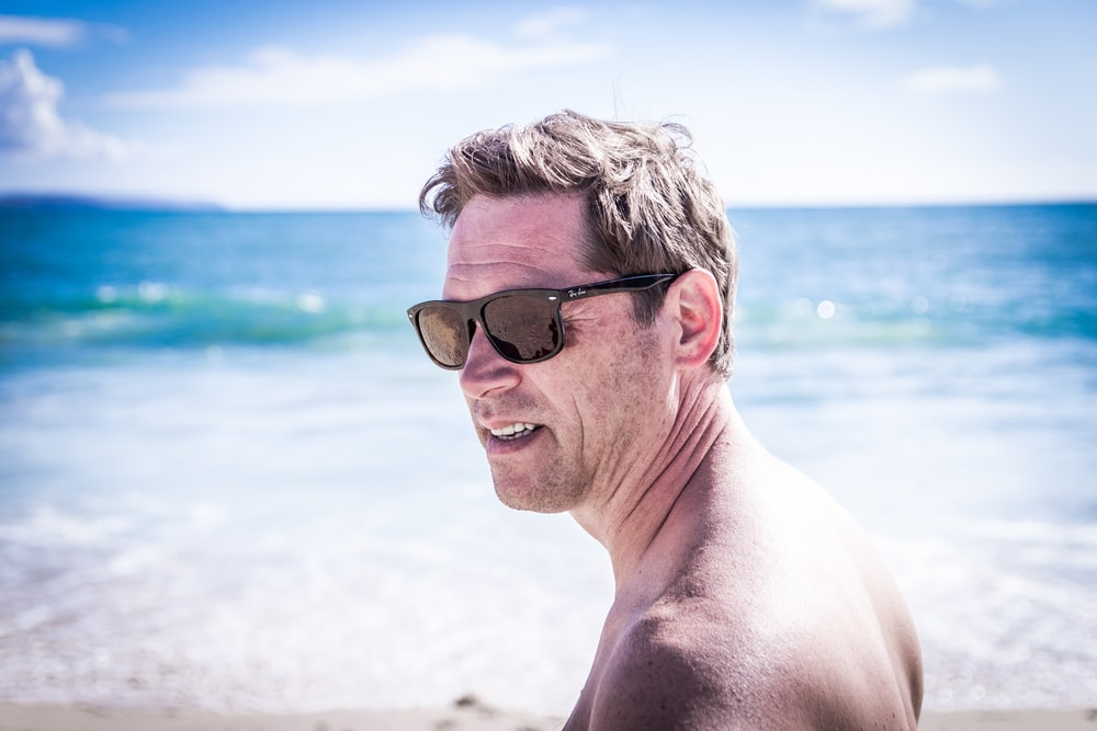 man wearing black-framed Wayfarer-style sunglasses standing near the body of water