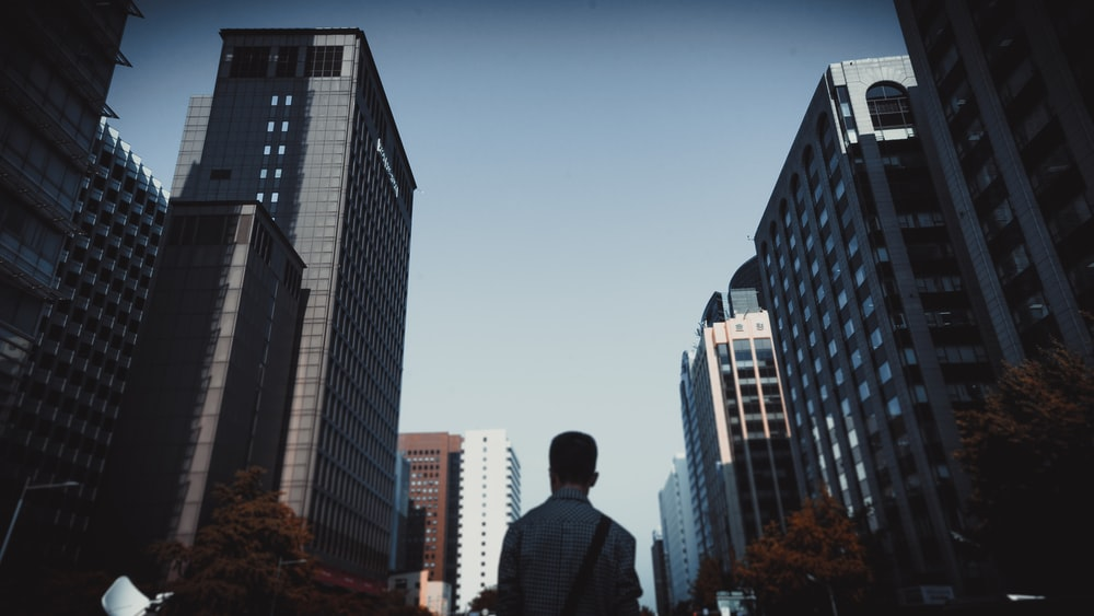 low angle photo of man standing between high-rise buildings under blue sky during daytime
