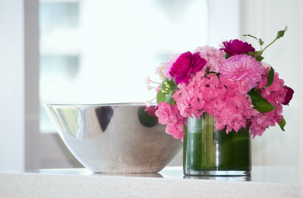 potted pink petaled flowers on table
