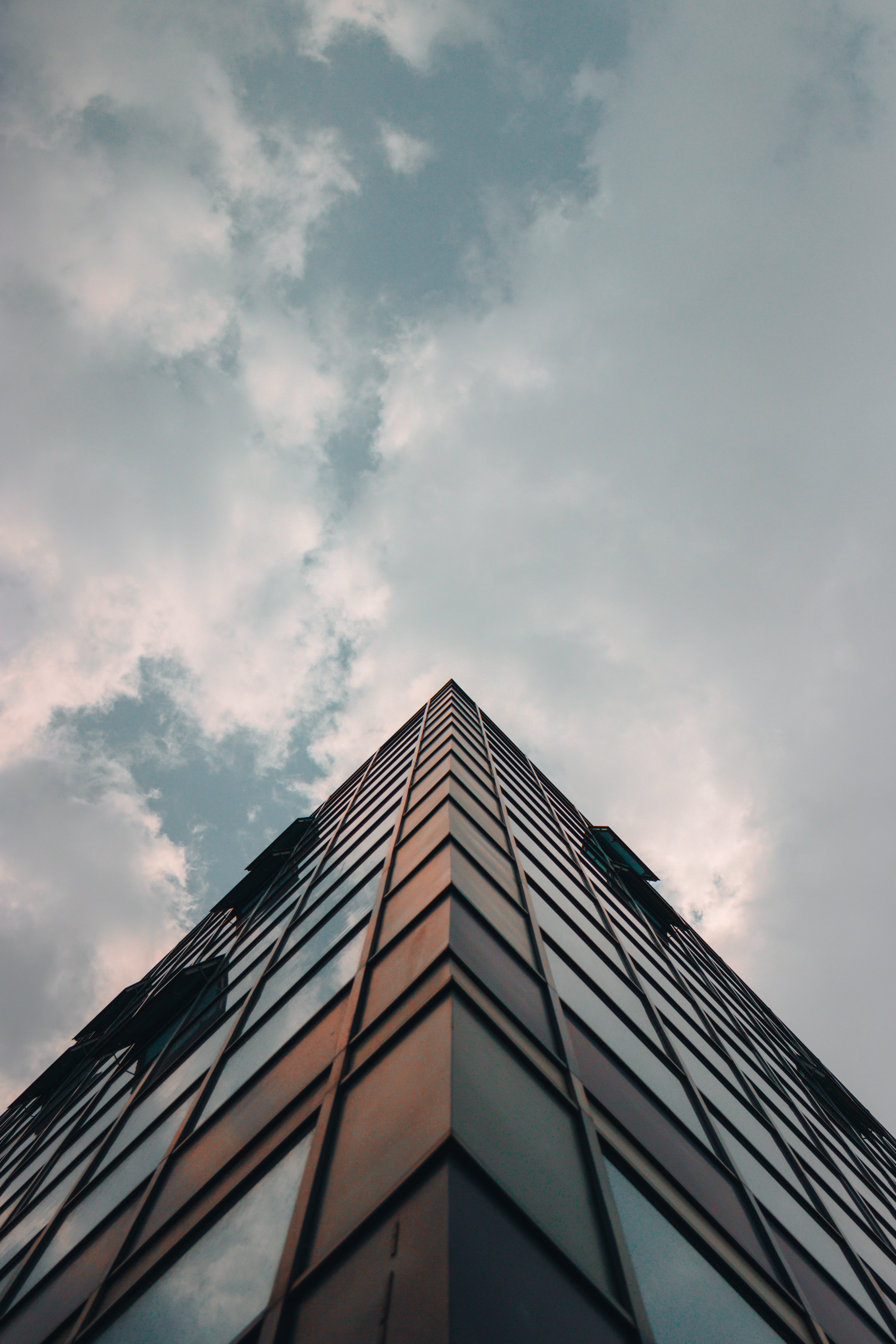 low-angle photography of glass building under thick clouds