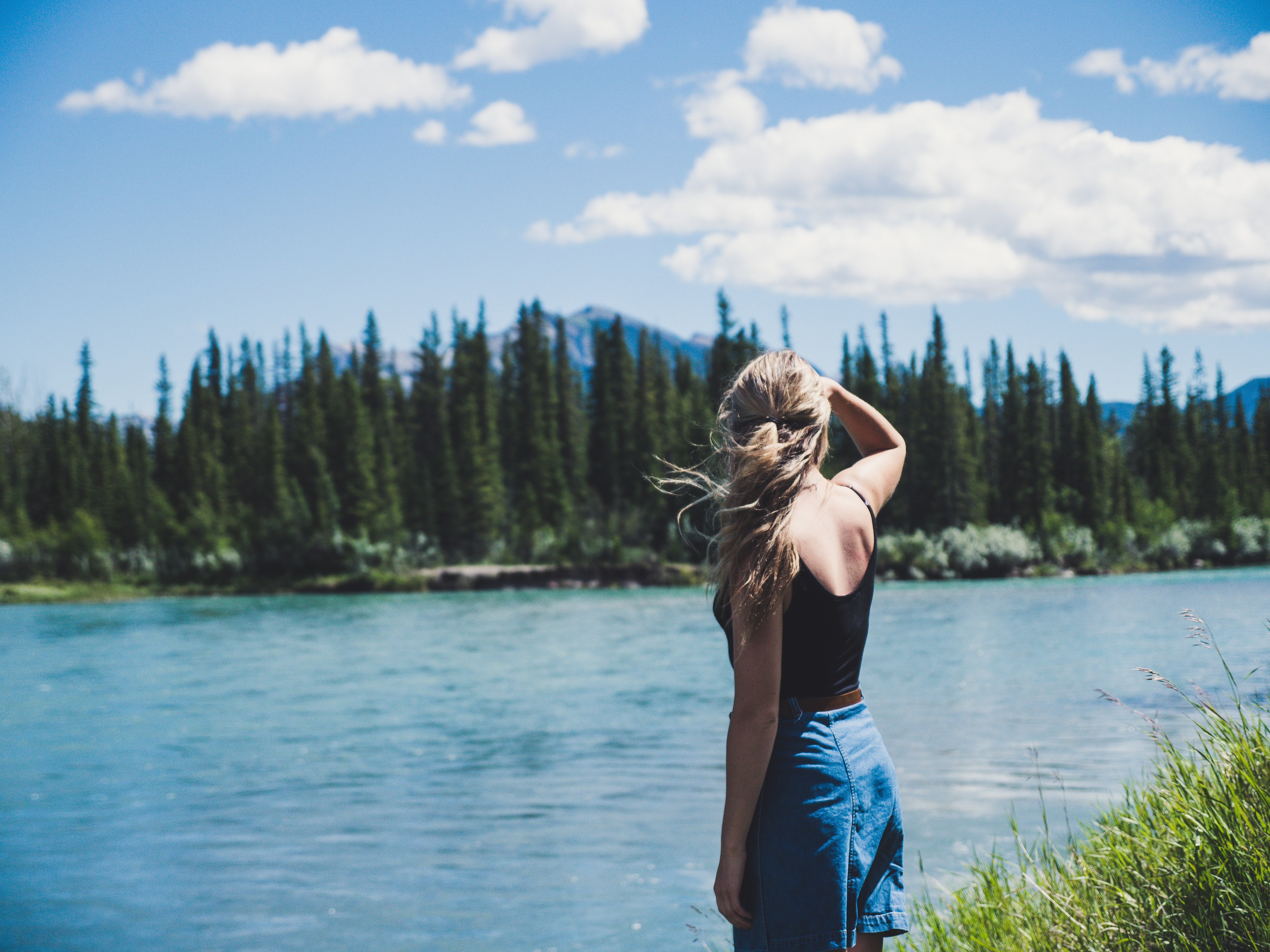 woman in black camisole standing near river