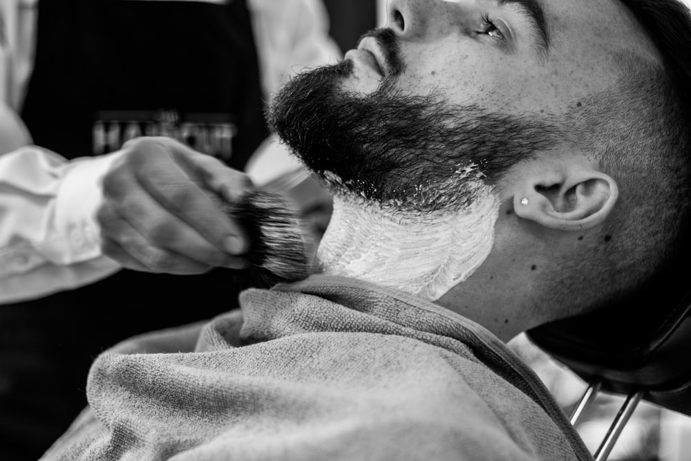 grayscale photo of man shaving his beard