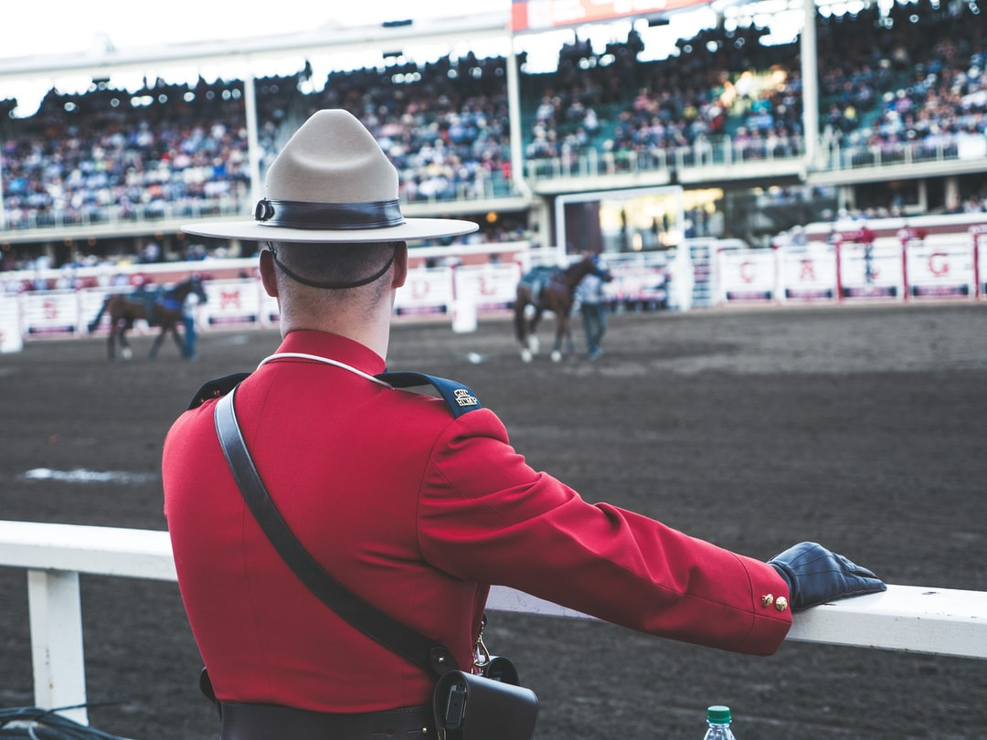 The Calgary Stampede is a great tradition in Calgary. People from all over the world travel to our city to take in the specticle full of western themed entertainment, music, carnival rides, games, food and fun. This moment of an RCMP officer in the traditional Mountie uniform, watching the horses at the chuckwagon races is a moment of calm after he accompanied our nations flag on stage for our national anthem, O'Canada.
