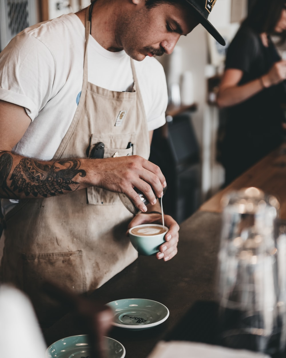 man pouring latte on coffee