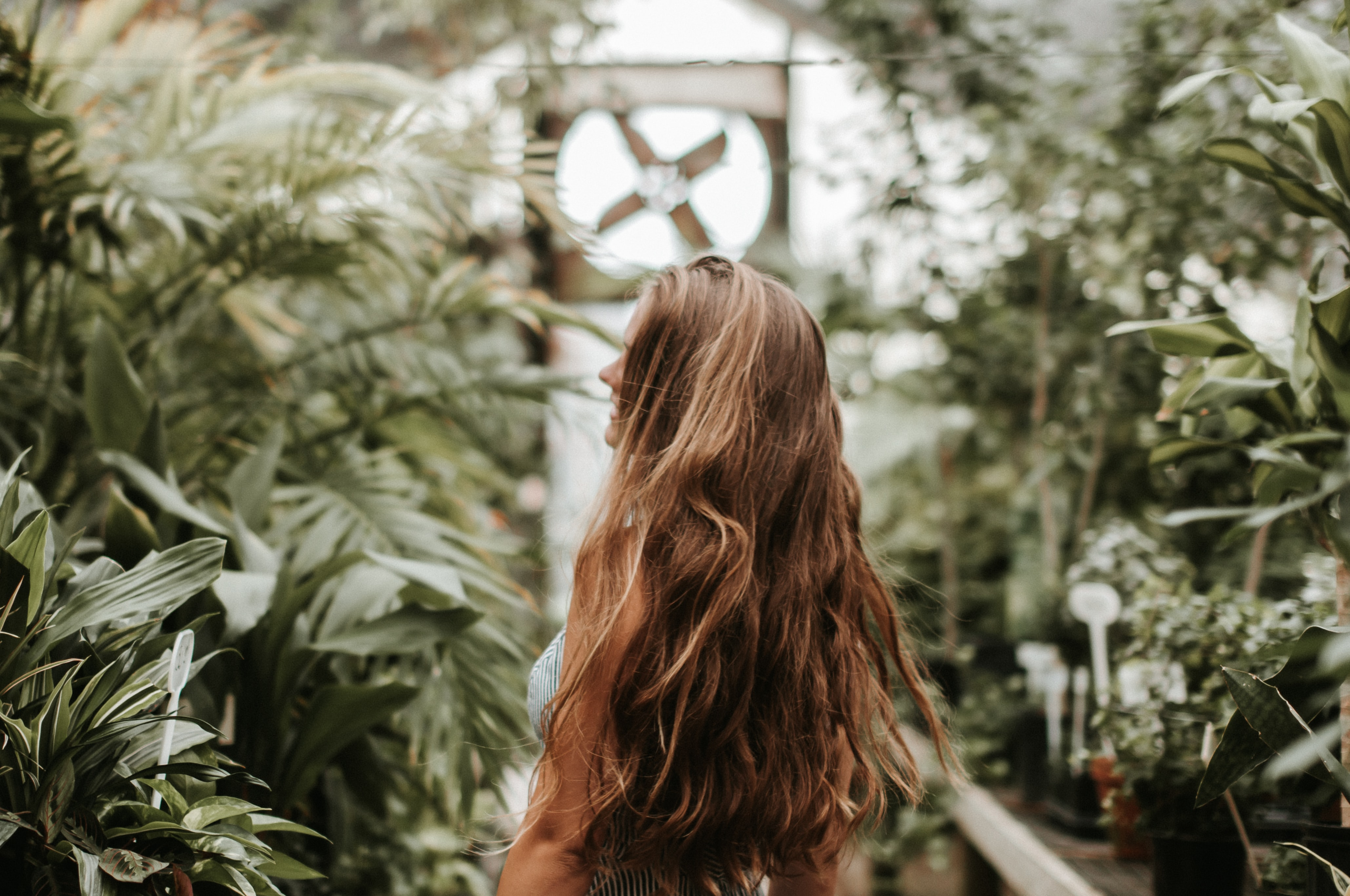 woman with strawberry blonde hair walking in the middle of green plants