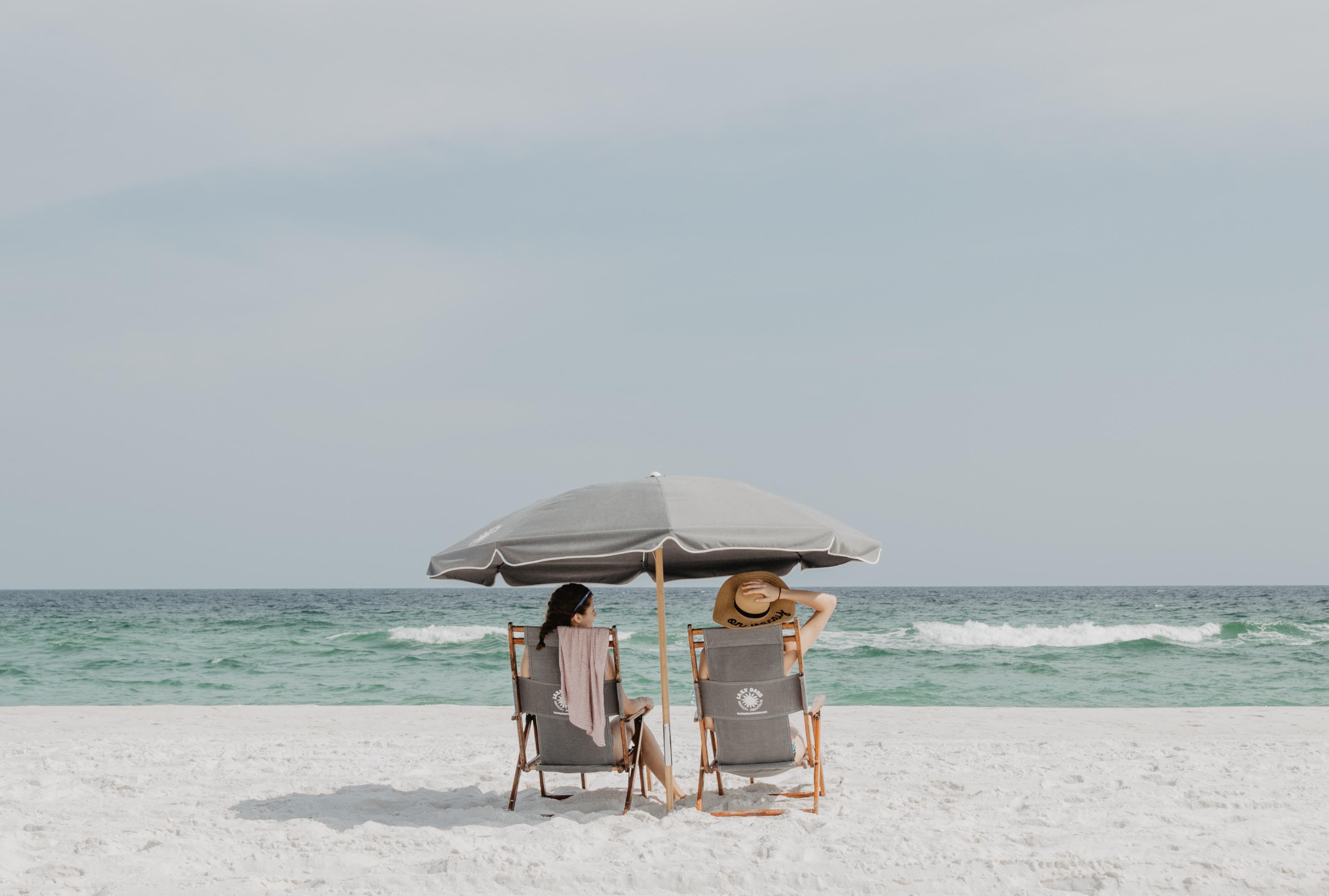 two people under beach umbrella near shoreline
