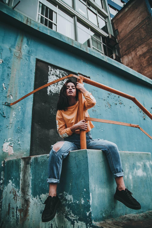 woman hugging post of orange metal railings during day