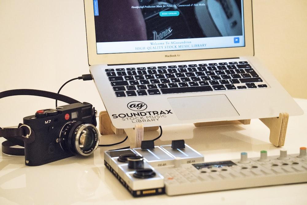 MacBook Air beside black M7 camera