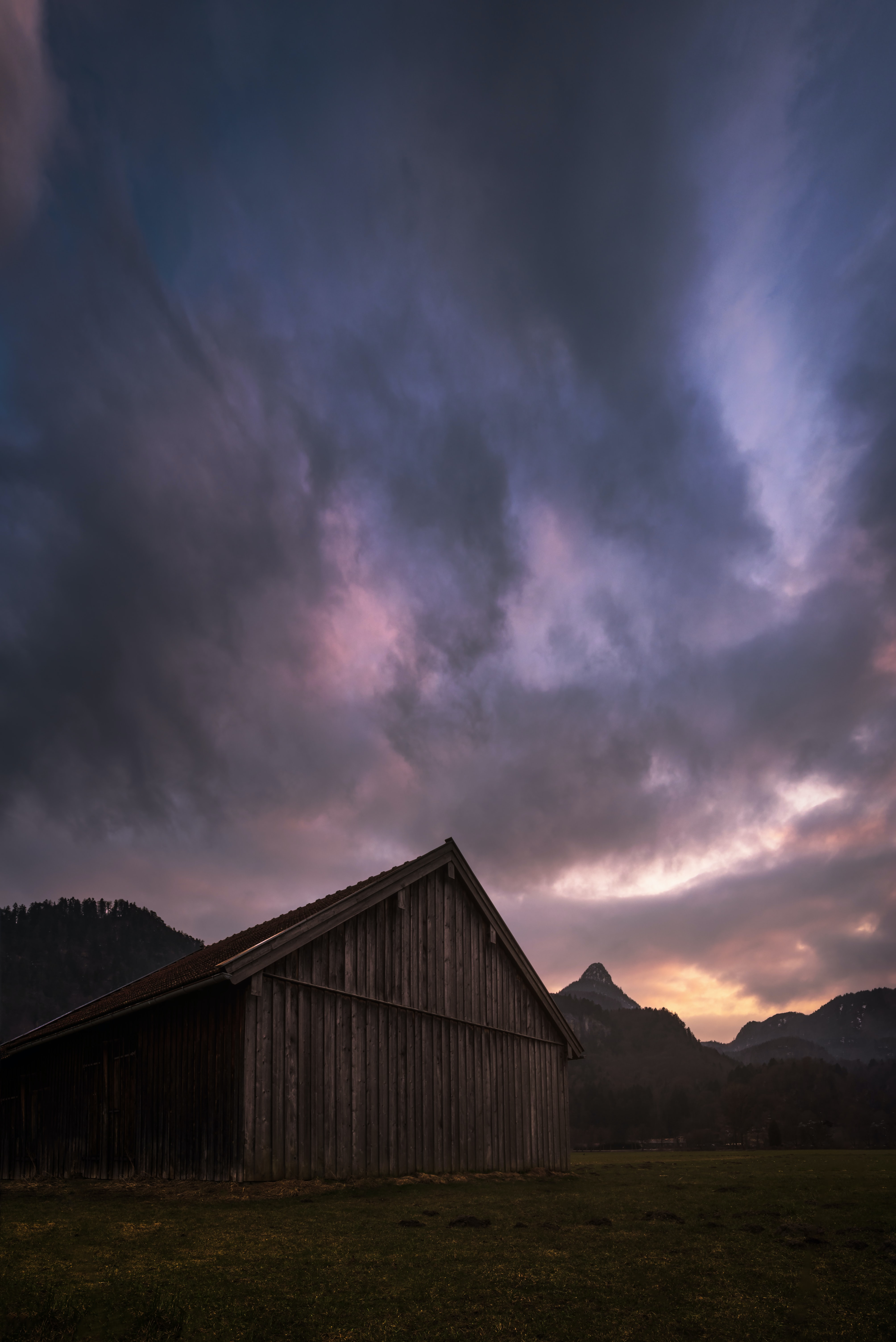brown wooden barn under gray clouds