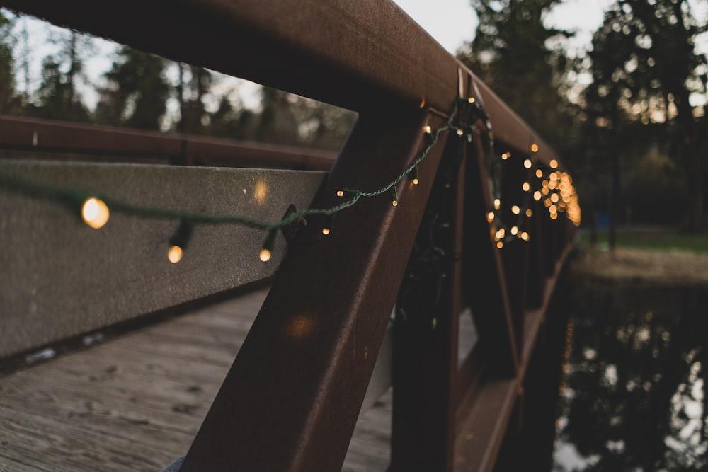 black and orange string lights hanged on brown wooden bridge