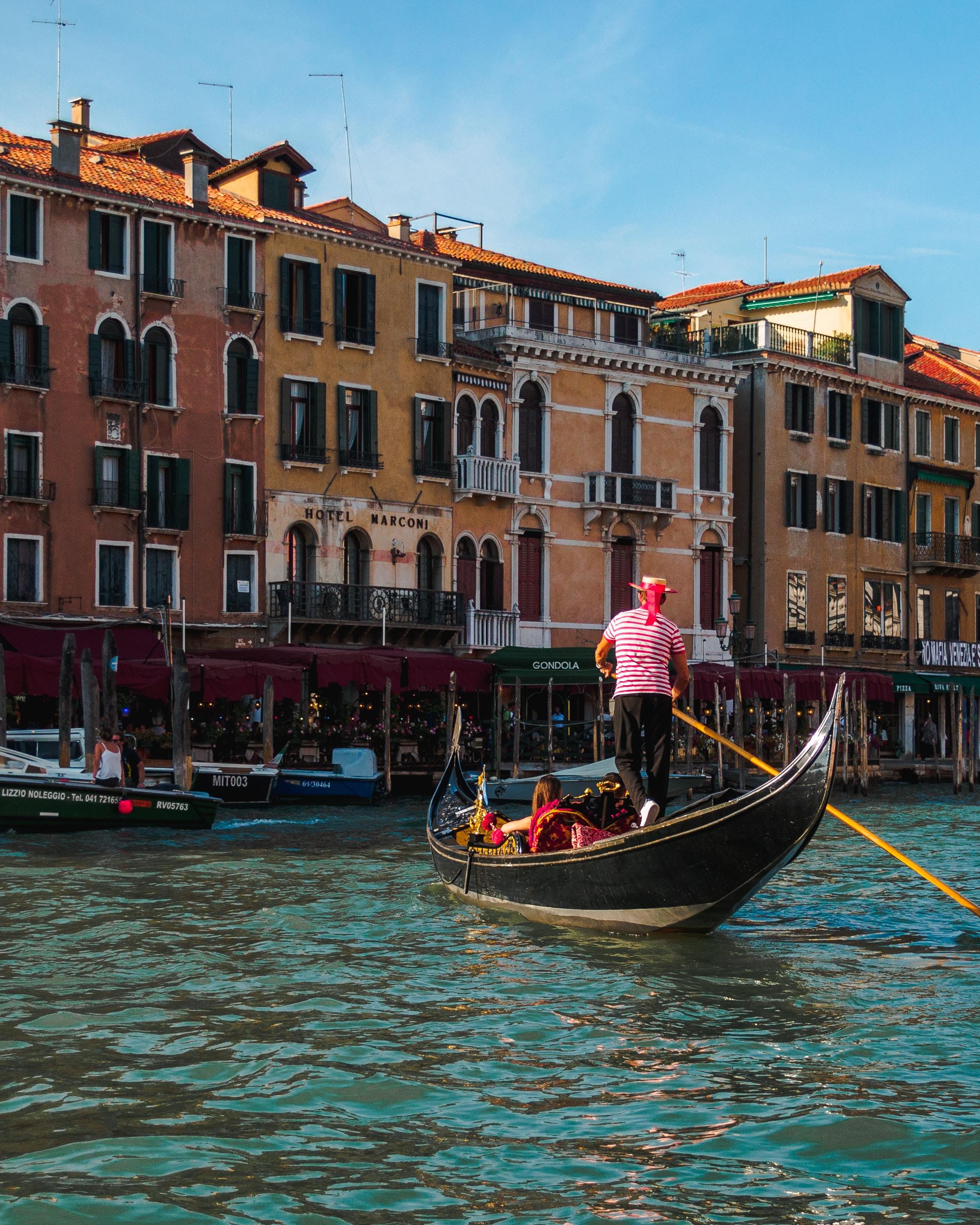 people riding boat beside buildings