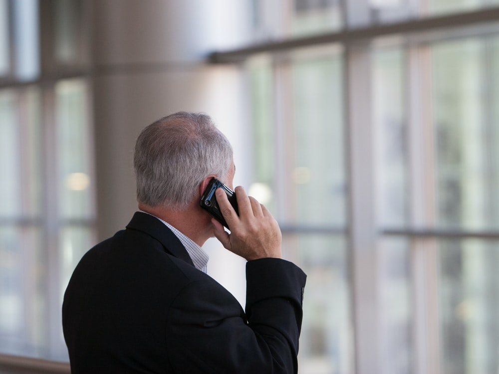 man holding black smartphone in front of a windowpane