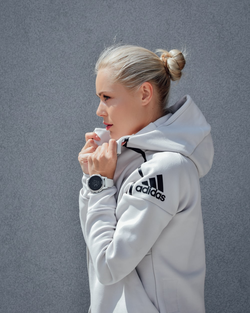 woman wearing gray and black adidas pullover hoodie walking near gray wall during daytime