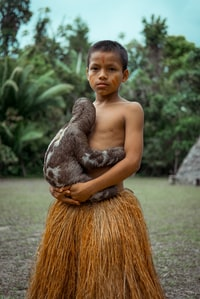 boy holding black and white sloth during daytime