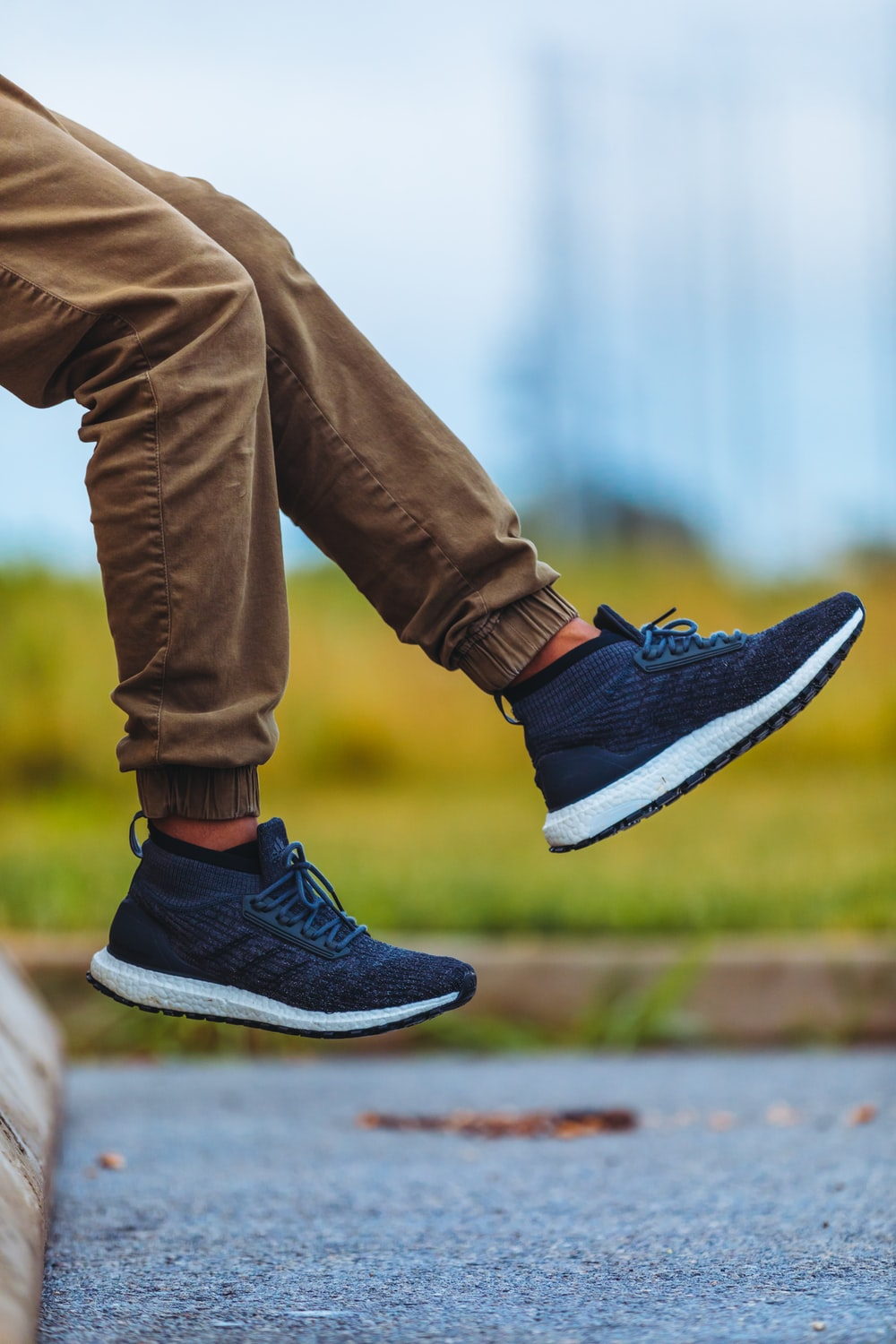 person wearing brown jogger pants and blue adidas running shoes during daytime