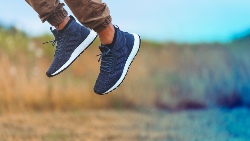 man wearing pair of blue-and-white adidas lace-up low-top sneaker leaping above ground at daytime