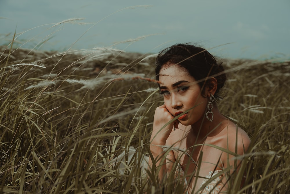 woman wearing brown top surrounded by grass during daytime