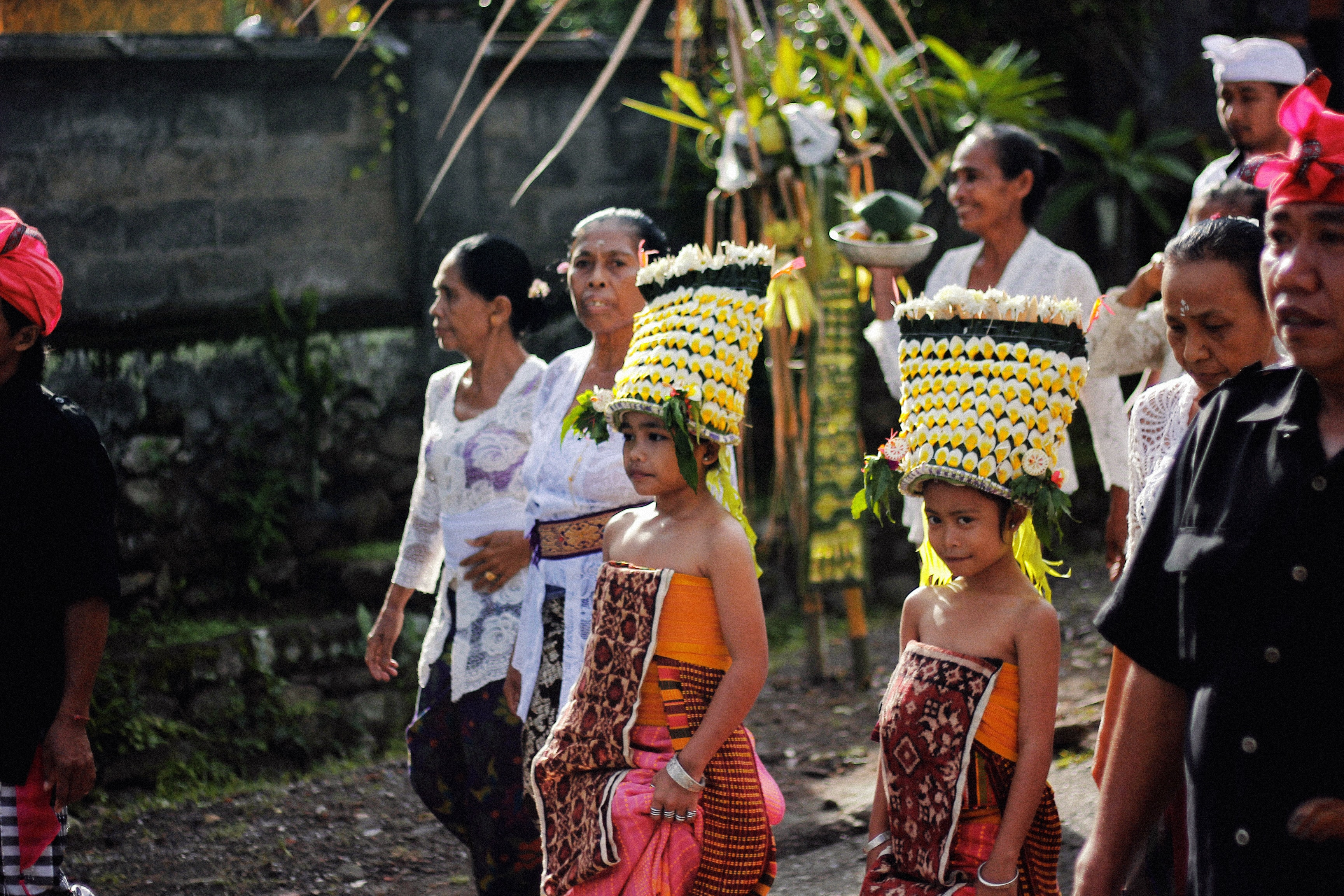 two girls wearing traditional attire parading on road with other people during daytime