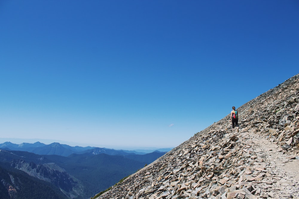 landscape photography of man standing on brown mountain