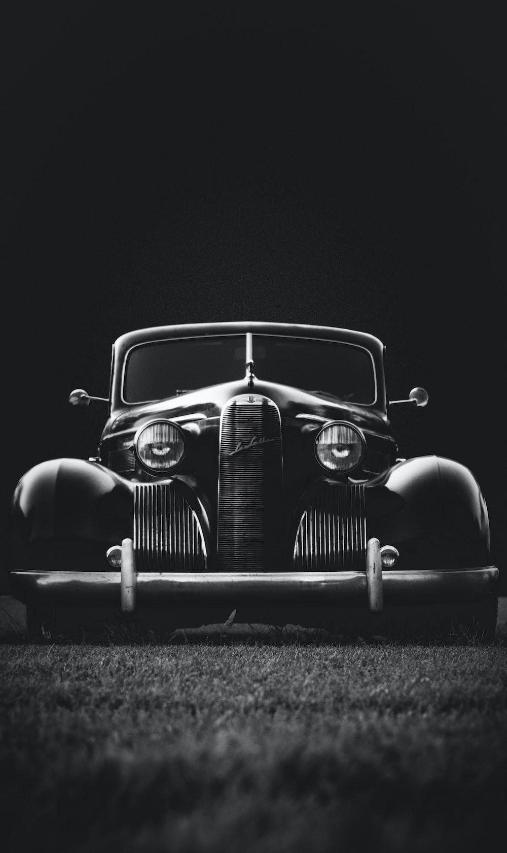 greyscale photo of classic vehicle on ground