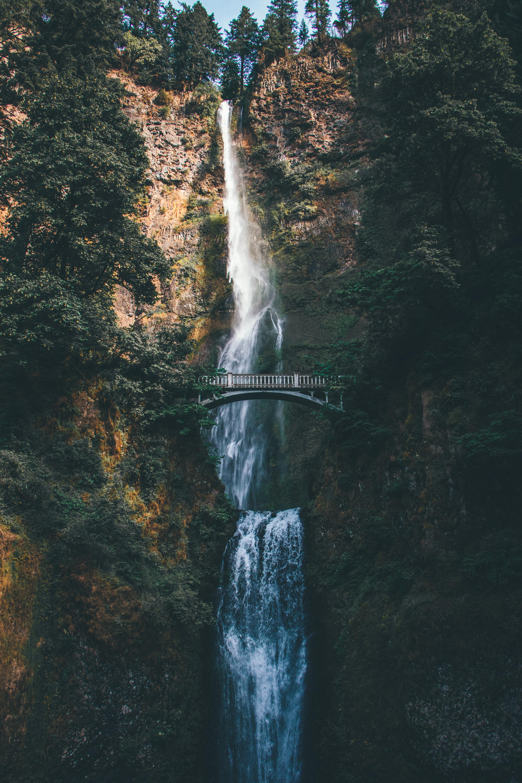 bridge overlooking waterfalls at daytime